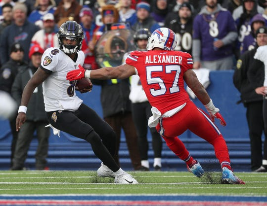 Ravens quarterback Lamar Jackson slips a tackle by Bills Lorenzo Alexander.