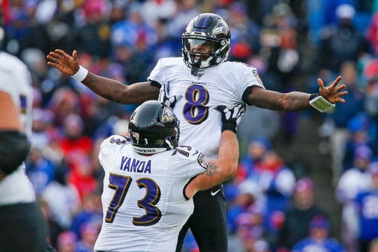 Baltimore Ravens quarterback Lamar Jackson (8) celebrates a 61-yard touchdown play with Marshal Yanda during the second half of an NFL football game against the Buffalo Bills in Orchard Park, N.Y., Sunday, Dec. 8, 2019. (AP Photo/John Munson)
