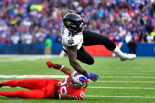 Baltimore Ravens running back Gus Edwards (35) is upended by Buffalo Bills cornerback Kevin Johnson (29) during the second half of an NFL football game in Orchard Park, N.Y., Sunday, Dec. 8, 2019.