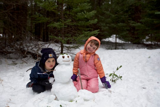 Making a snowman while searching for a Christmas tree to cut from Oregon's Willamette National Forest.