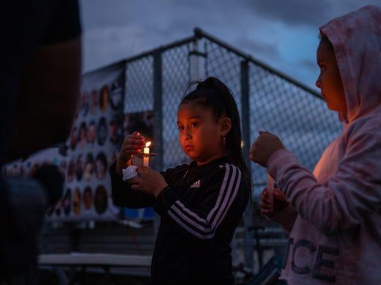 Marysa Lizama, a la izquierda, de pie junto a su hermana Maya Lizama, mientras ambas tratan de que no se apaguen las llamas de sus velas durante el 15° evento de Encendido del Árbol de Navidad y Vigilia de Conmemoración para honrar a las víctimas que han perdido la vida debido a la violencia, en Closter Park, en la zona este de Salinas el 7 de diciembre de 2019.