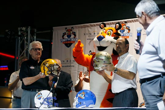 John Folmer, left, holds the Arizona State helmet and Stuart Sliva holds the Florida State helmet during the Tony the Tiger Sun Bowl announcement Sunday, Dec. 8, at Sunland Park Racetrack and Casino in El Paso. The Sun Bowl picked the brand name from the ACC, taking 6-6 Florida State to match up with Arizona State in the New Year's Eve game.