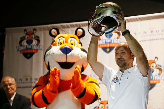 Stuart Sliva holds up the Florida State helmet during the Tony the Tiger Sun Bowl announcement Sunday, Dec. 8, at Sunland Park Racetrack and Casino in El Paso. The Sun Bowl picked the brand name from the ACC, taking 6-6 Florida State to match up with Arizona State in the New Year's Eve game.