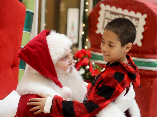 "Elijah Vega, 9, of Garnerville spends time with Santa Claus during a special visit with Santa at the Palisades Center Mall in West Nyack Dec. 8, 2019. The visit, arranged especially for children on the autism spectrum, is a program called Santa Cares, and is a partnership between Autism Speaks and Cherry Hill Programs, which supplies ""authentic, real-bearded Santas"" to more than 900 locations in the U.S., Canada and Puerto Rico. The program allows autistic and special needs children to meet and be photographed with Santa Claus in a less-stressful atmosphere, without waiting in long lines, and taking place at times when the mall is not crowded."