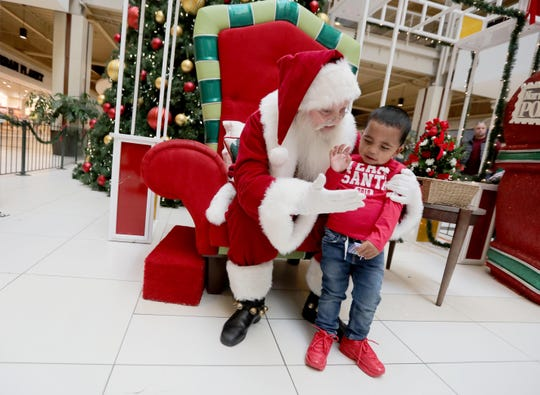 "Damien Ardzu, 2, of the Bronx gives a high five to Santa Claus during a special visit with Santa at the Palisades Center Mall in West Nyack Dec. 8, 2019. The visit, arranged especially for children on the autism spectrum, is a program called Santa Cares, and is a partnership between Autism Speaks and Cherry Hill Programs, which supplies ""authentic, real-bearded Santas"" to more than 900 locations in the U.S., Canada and Puerto Rico. The program allows autistic and special needs children to meet and be photographed with Santa Claus in a less-stressful atmosphere, without waiting in long lines, and taking place at times when the mall is not crowded."