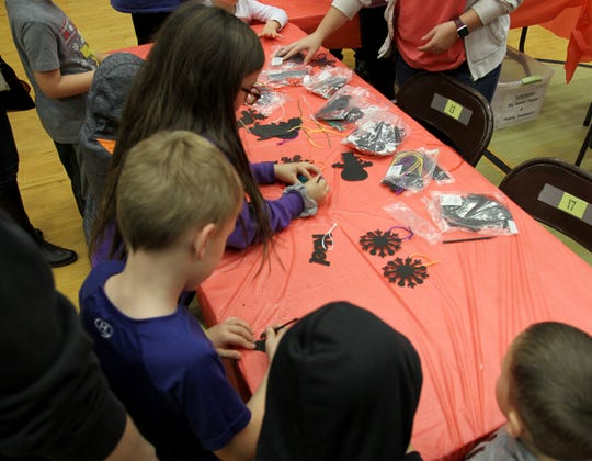 Children make ornaments at Christmas in the Park Saturday, Dec. 7, 2019, at Scotland Elementary.