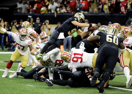 New Orleans Saints quarterback Drew Brees (9) leaps to score a touchdown against the San Francisco 49ers