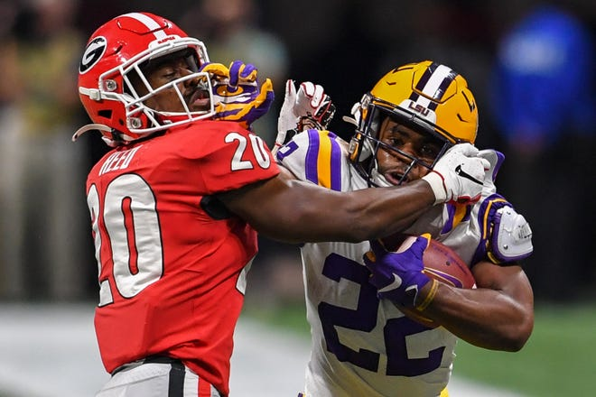 LSU Tigers running back Clyde Edwards-Helaire stiff-arms Georgia Bulldogs defensive back J.R. Reed during the second half of the SEC championship game.
