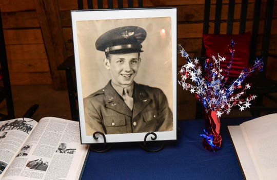 A photo of Charles Horne, Jr. of Honea Path during his military service with the U.S. Army Air Forces is shown at a table during a ceremony at the Barn at Green Acres in Honea Path Monday. Horne, 95, was presented The Legion of Honor by Vincent Hommeril, Consulate General of France based in Atlanta.
