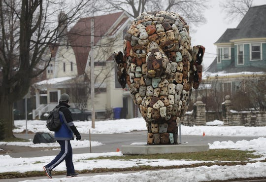 "A pedestrian looks at ""The Collective,"" a sculpture by Paul Bobrowitz, while walking along East College Avenue. Critics have questioned the suitability of the artwork in a neighborhood of historic homes."