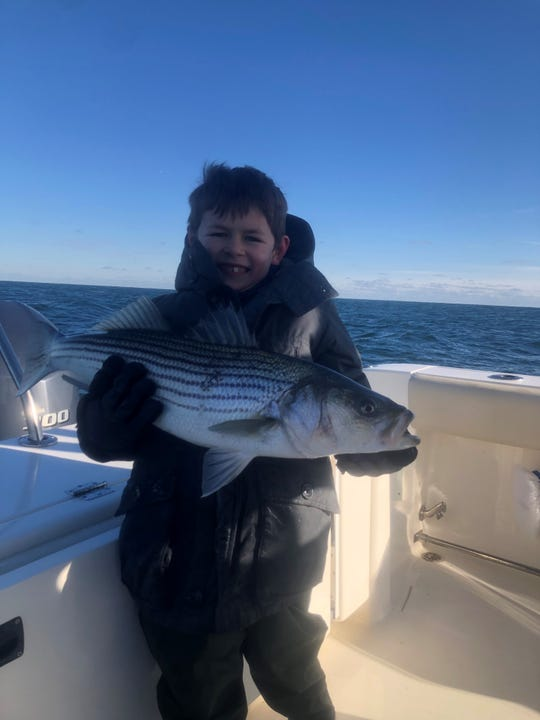 A.J. Whiting, 7 of Brielle, with a keeper striped bass he caught fishing with his dad on Saturday.