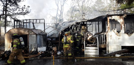 Firefighters inspect a home in the aftermath of a fire in Manchester.