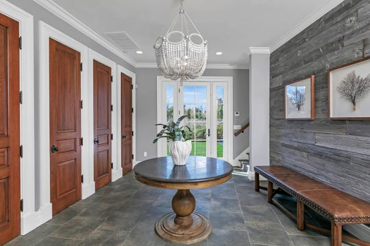 The foyer features tile flooring and a custom door.