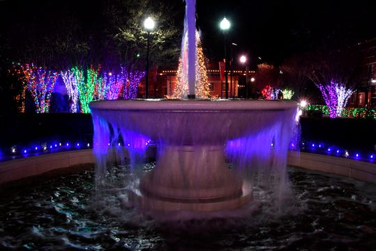 Holiday lights illuminate the water spilling over the Everman Park fountain.