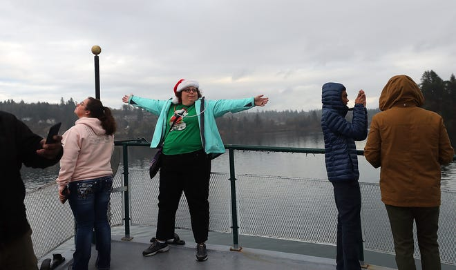 Amy Owens, center, spreads her arms out wide in the wind and the mist as she takes in the view from the bow of the Carlisle II as it heads away from the dock and into Dyes Inlet during the Special People's Cruise hosted by the Bremerton Yacht Club on Sunday.