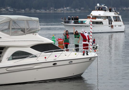 Santa and his elves wave to the boats passing by while anchored in Dyes Inlet for the Special People's Cruise hosted by the Bremerton Yacht Club on Sunday.