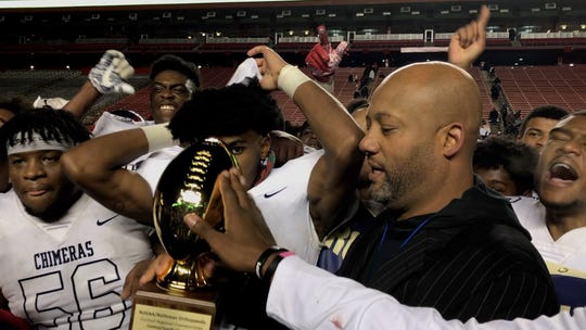 Willingboro coach Steve Everette , right, holds the regional championship trophy after Chimeras' 50-14 win over Penns Grove