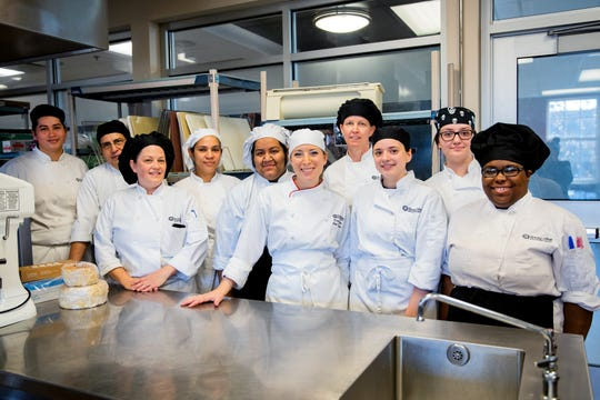 Pastry chef and instructor Diane Fehder (fifth from right) gathers in the kitchen of the Culinary Arts Center of Rowan College at Burlington County in Mount Holly with students and other faculty.