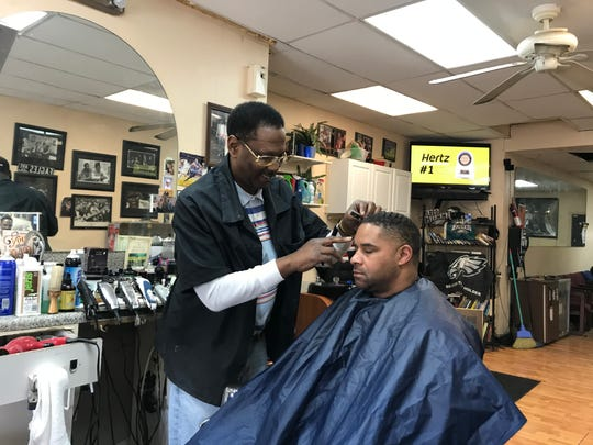 "Todd ""TI"" Israel works in his Haddon Avenue barbershop in December. His business has had to close in the midst of the COVID-19 pandemic and he worries about his future."