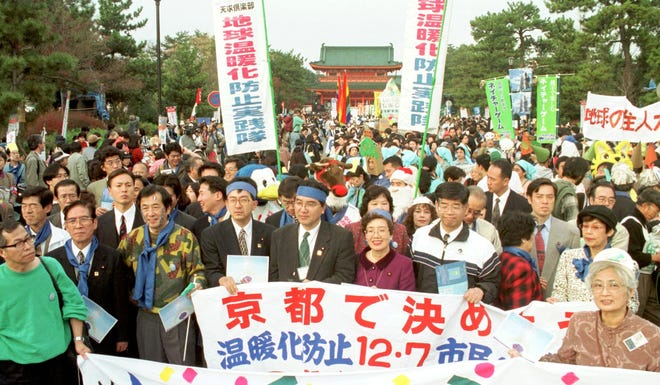 Environmentalists and citizens hold banners and start a parade calling for reduction of the green house gas emissions in front of the Heian Jingu shrine in Kyoto, western Japan, Sunday, Dec. 7, 1997. Representatives from 150 countries gather in this Japanese ancient capital and continue negotiations over controlling energy use in the 21st century to protect the Earth.