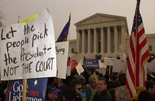 Protesters hold signs and flags in front of the U.S. Supreme Court in Washington, Monday, Dec. 11, 2000. The court will hear arguments on an appeal by Republican candidate Texas Gov. George W. Bush to stop the hand recount of presidential ballots in Florida. The court ordered the recount stopped on Saturday.