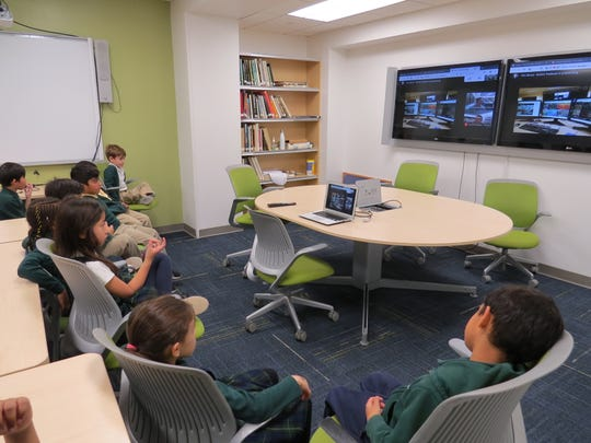Wardlaw+Hartridge first graders sit and listen to weather experts during their Skype session in the school's Center for Global Learning.