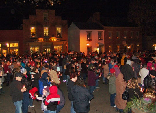 Visitors hold candles during the Christmas Candlelighting ceremony in Roscoe Village on Saturday.