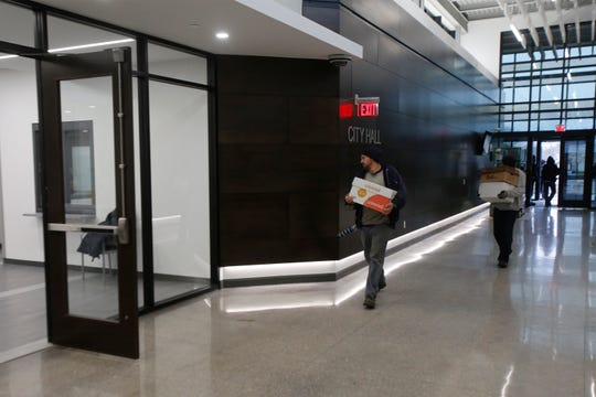 Workers carry boxes into the new Altoona City Hall and Police Department. The Altoona City Council will hold its first meeting inside the new building on Monday.