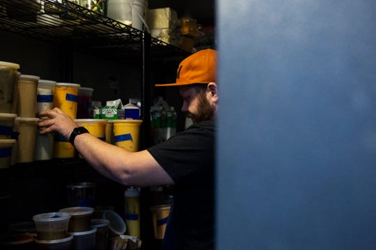 Sean Wilson, director of culinary operations for the Justice League of Food, makes sure items in a walk-in fridge are organized in The Kitchen DSM on Monday, Dec. 9, 2019, at The Hall in West Des Moines.