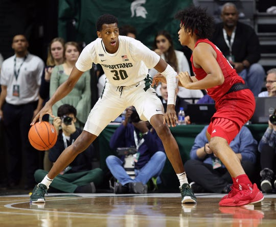 Michigan State forward Marcus Bingham Jr. is defended by Rutgers guard Ron Harper Jr. during the first half Sunday, Dec. 8, 2019, in East Lansing.