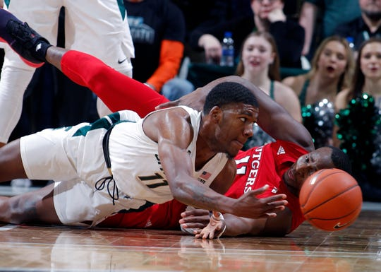 Michigan State's Aaron Henry and Rutgers' Mamadou Doucoure scramble for a loose ball during the first half Sunday, Dec. 8, 2019, in East Lansing.