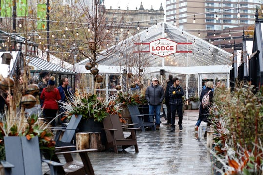 People pass holiday markets in Cadillac Square on Sunday, Nov. 18, 2018 in Detroit.