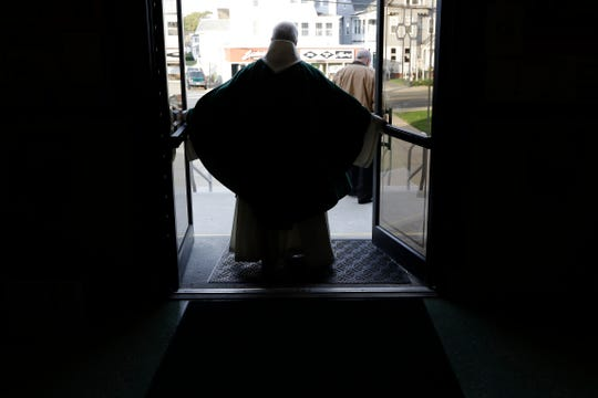 In this Sunday, Oct. 20, 2019 photo Rev. William Tourigny, pastor of St. Rose de Lima Parish, in Chicopee, Mass., closes the Catholic church's front doors following Mass.