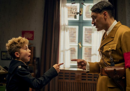 """This image released by Fox Searchlight Pictures shows, from left, Roman Griffin Davis and Taika Waititi in a scene from the WWII satirical film """"Jojo Rabbit."""" On Monday, Dec. 9, 2019, Davis was nominated for a Golden Globe for best actor in a motion picture comedy for his role in the film."""