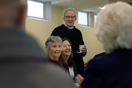 In this Sunday, Oct. 20, 2019 photo Rev. William Tourigny, top, pastor of St. Rose de Lima Parish, in Chicopee, Mass., meets with parishioners for coffee and donuts in the Catholic church's basement following Mass.