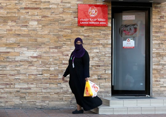 A woman leaves a ladies only service area at a restaurant in Saudi Arabia. Women there will no longer need to use separate entrances.