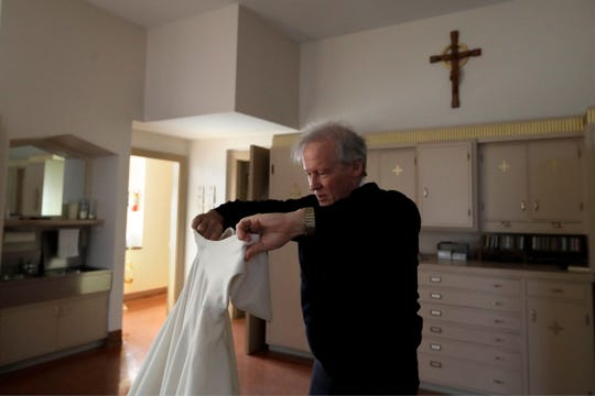 In this Sunday, Oct. 20, 2019 photo Rev. William Tourigny, 66, pastor of St. Rose de Lima Parish, in Chicopee, Mass., puts on vestments while preparing to offer Mass at the Catholic church.
