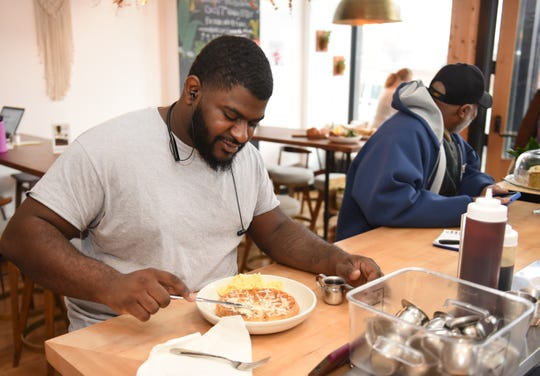 Customer Terry Harris of Warren enjoys a house waffle at Folk restaurant in Corktown.