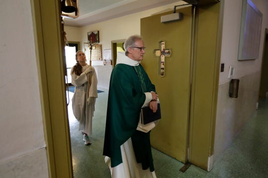 In this Sunday, Oct. 20, 2019 photo Rev. William Tourigny, front, pastor of St. Rose de Lima Parish, in Chicopee, Mass., processes toward the altar to offer Mass at the Catholic church.