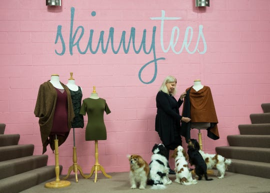 Linda Schlesinger-Wagner, Founder/CEO of Skinnytees, adjusts a garment in her studio, while in the company of her rescue dogs at her shop in Birmingham Michigan.
