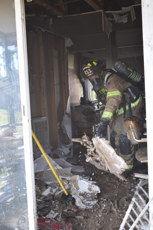 San Carlos Park Fire District firefighters search through a house that caught fire Monday afternoon. The fire marshal has determined it was accidental and began in a utility closet which contained the water heater, air handler, washer and dryer.