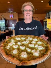 Maria LaMotta, a founder of the 40-year-old LaMotta's Italian Restaurant in south Fort Myers, shows off one of her family's signature pizzas.
