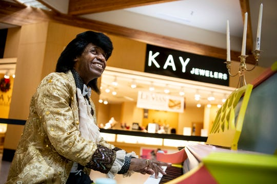 In this recent photo, Asaph Adonai impersonates Liberace as he plays the piano at the Southgate Mall in Missoula, Mont. This is Adonai's 10th year entertaining holiday shoppers at the mall. (Ben Allen Smith/The Missoulian via AP)