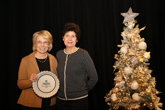 Barbara Wells of the Union County Farm Bureau Women's Committee, accepts the 2019 Gold Star Award of Excellence from Vicki Bryant, chair of the Kentucky Farm Bureau state Women's Committee. The award was presented during a December 6 recognition program at the 100th Kentucky Farm Bureau annual meeting.