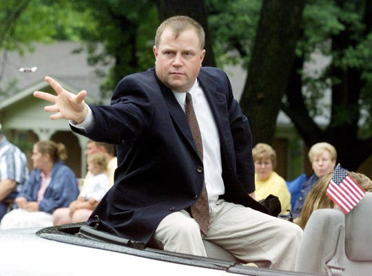 Richard Jewell, parade grand marshal, tosses candy to spectators along the parade route in Carmel, Ind., Wednesday, July 4, 2001.