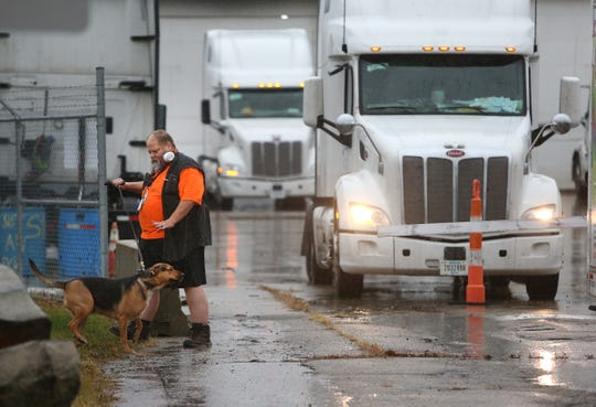 Former Celadon truck driver Jack Jobes of Pensacola, Florida walks his dog Bella Monday at Celadon on East 33rd Street. Jobes rented a U-Haul van for transportation after turning in his semi truck to the company.