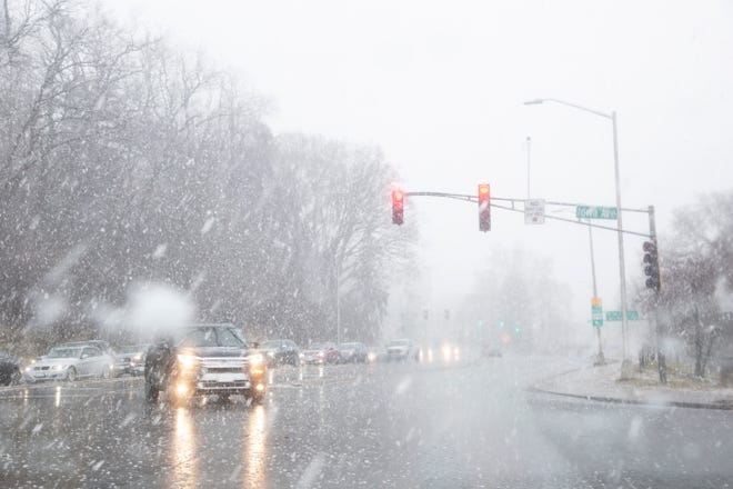 A truck turns onto Iowa Avenue as snow falls, Monday, Dec. 9, 2019, along Riverside Drive in Iowa City, Iowa.