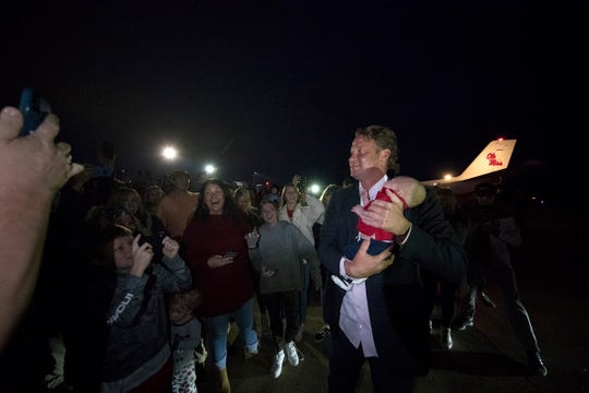Ole Miss football coach Lane Kiffin holds a baby after he arrives at the Oxford airport on Sunday night.