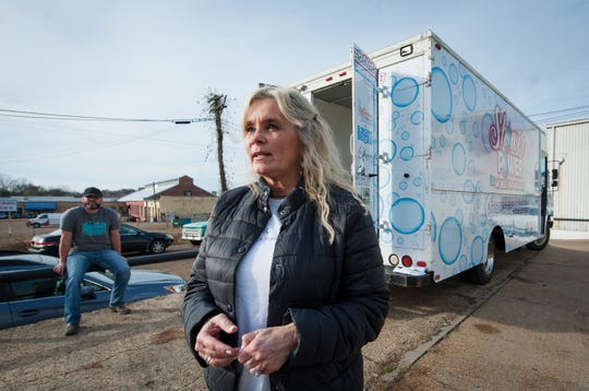 Teresa Renkenberger of Flowood, Miss., describes the inspiration for her Shower Power Mobile Shower Unit for the homeless. Kevin Poe, of Florence, background, converted the food truck to a mobile shower unit. The two were in Jackson on Dec. 5, 2019, where she makes the mobile shower available weekly.