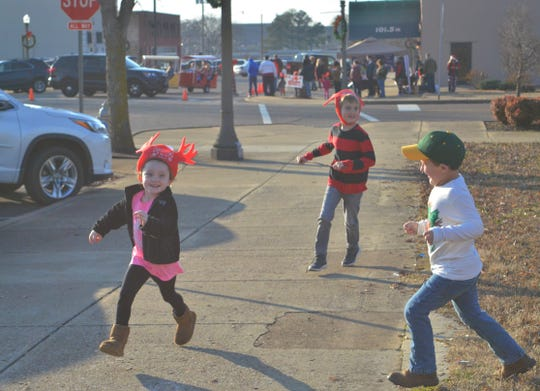 McKinley King, 6, left, plays a game of tag with friends while she waits to meet Santa at Jackson's Christmas in the City event on Dec. 7, 2019.